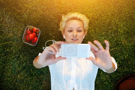 Photo for Top view of pretty young woman making self portrait on mobile phone while resting on grass plot in summer day, attractive female student taking picture with cell telephone camera while lying on a lawn - Royalty Free Image