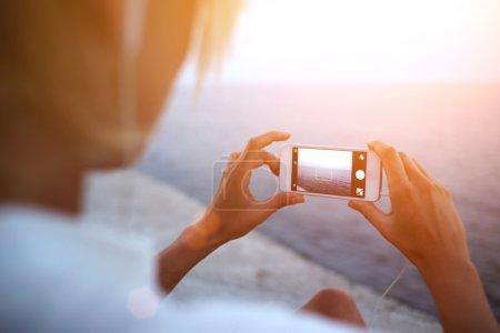 woman taking picture of ocean landscape