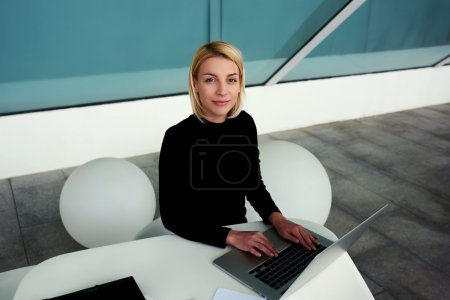 woman posing while working on laptop computer