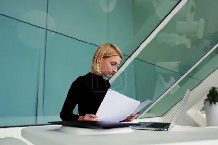 businesswoman reading paper documents