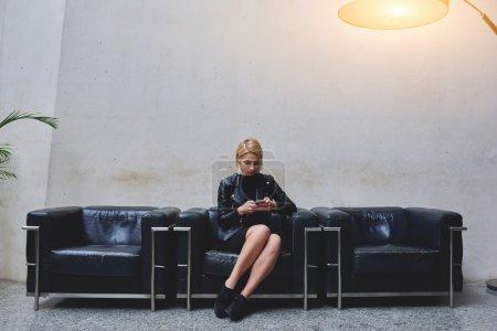 Photo pour Jolie femme aux cheveux blonds écrivant un message texte sur son téléphone portable en attendant une réunion à l'intérieur du bureau, la jeune femme tendance vérifie les prévisions météorologiques sur son téléphone portable pendant la pause de travail - image libre de droit