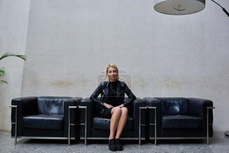 Photo pour Belle jeune fille hipster posant assis sur un canapé en cuir noir à l'intérieur du bureau moderne, charmante femme habillée de vêtements élégants reposant dans le couloir avant de rencontrer ses meilleurs amis - image libre de droit