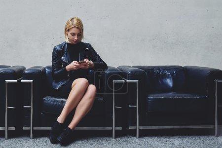 Photo pour Jeune belle femme assise dans le couloir avec téléphone portable et de revoir dans les séances de cinéma en réseau le soir, fille hipster écriture message texte sur téléphone cellulaire avant de rencontrer son ami - image libre de droit