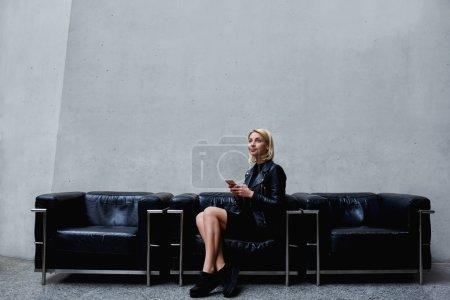 Photo pour Femme réfléchie attendant un message texte sur son téléphone portable assis dans le couloir du bureau moderne, jeune femme branchée tenant un téléphone portable tout en pensant à une réunion réussie avec l'employeur - image libre de droit