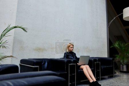 Photo pour Jolie jeune femme avec l'ordinateur portable ouvert sur des genoux s'asseyant dans le couloir avant de vérifier dans la chambre d'hôtel, fille de hipster à la mode regardant des vidéos sur le net-book portatif tout en se reposant dans le couloir de bureau - image libre de droit
