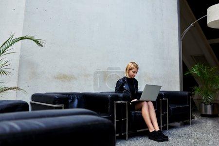 Photo pour Étudiante élégante utiliser net-book pour le travail à distance tout en étant assis sur un canapé en cuir confortable dans l'intérieur moderne, femme expérimentée pigiste assis sur le coach et se connectant à sans fil via ordinateur portable - image libre de droit