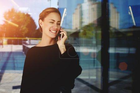 Photo pour Sourire de femme d'affaires, parler au téléphone portable en mains en se tenant debout à l'extérieur près d'immeuble de bureaux - image libre de droit
