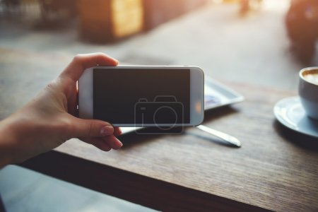 Photo pour Closeup image of female hand holding mobile phone with blank copy space screen for your text message or promotional content, young female watching video via cell telephone while sitting in cozy cafe - image libre de droit