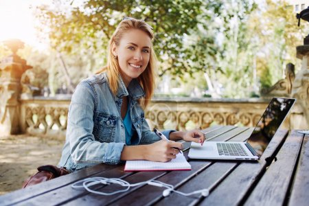 Photo for Young woman smiling to camera while sitting with notepad and laptop computer in beautiful city park, happy Caucasian female posing during work on portable netbook outdoors in warm spring day - Royalty Free Image