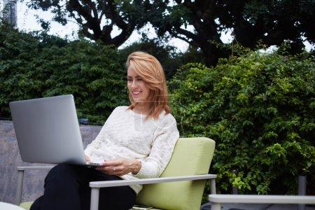 Photo pour Femme gaie regardant vidéo drôle sur ordinateur portable en attendant son ordre dans un café confortable trottoir, souriant fille hipster bavarder avec des amis en réseau via net-book tout en se détendre dans un café - image libre de droit