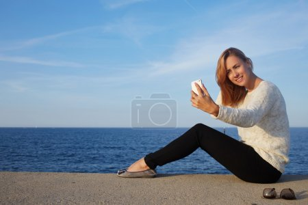 hipster girl making photo on mobile phone