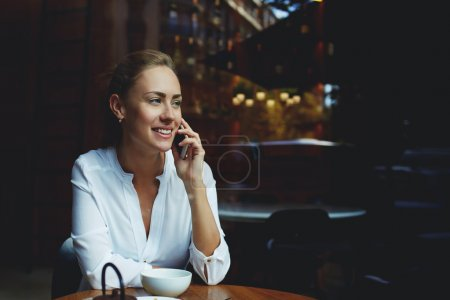 Photo for Cheerful female talking on mobile phone with friend while sitting with cup of cappuccino in modern coffee shop, smiling businesswoman having nice cell telephone conversation during work break in cafe - Royalty Free Image