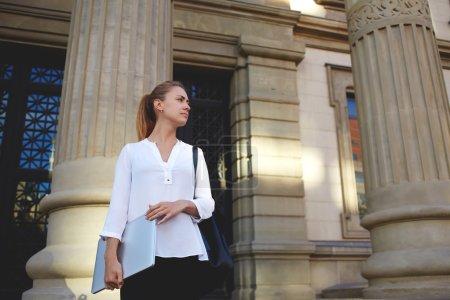 Photo pour Jeune femme confiante avec netbook fermé attendant l'employeur tout en se tenant près de l'immeuble de bureaux d'architectes, belle femme tutrice debout avec ordinateur portable près de l'université avant de commencer la leçon - image libre de droit