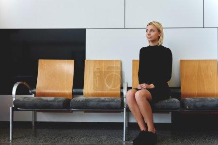 Photo pour Charmante jeune femme attendant quelqu'un assis dans le couloir du bureau - image libre de droit