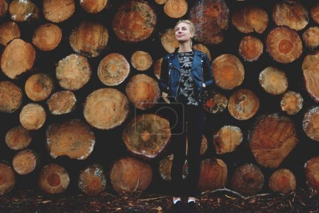 Girl against stacked wooden logs