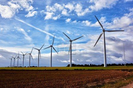 Foto de Turbinas eólicas blancas en el campo contra el cielo azul nublado en el día de primavera, generadores eléctricos en el campo, molinos de viento en el trabajo fuera de la ciudad - Imagen libre de derechos