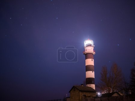 Black and white lighthouse at night in Baltic sea ...