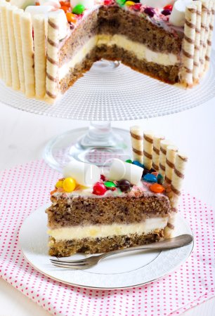 Photo for Banana layered cake with cream and yogurt filling, decorated with candies and marshmallows - Royalty Free Image
