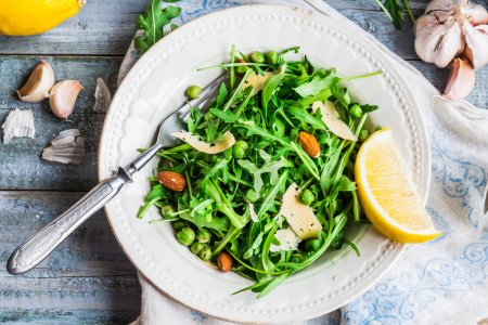 Photo for Fresh green salad with arugula, cheese, almonds, lemon and olive oil, healthy food,top view - Royalty Free Image