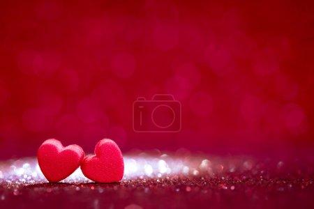 Photo pour Les formes de coeur rouges sur fond de paillettes de lumière abstraite dans le concept de l'amour pour la Saint Valentin avec un moment doux et romantique - image libre de droit