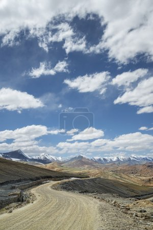 View of curved road among snow capped mountains