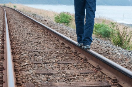 Photo for Legs of person walking on train tracks - Royalty Free Image