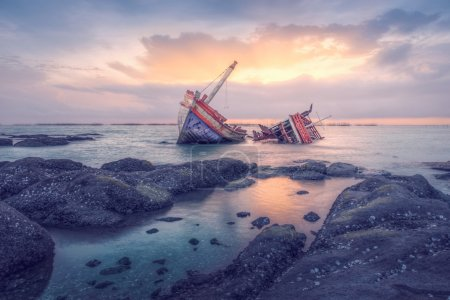 Ancient shipwrecks in the sea with sunset backgrou...