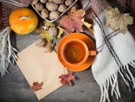 Autumn still life with cup of tea, plaid and leaves