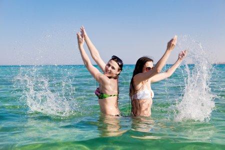 junge Frau streut Wasser ins Meer