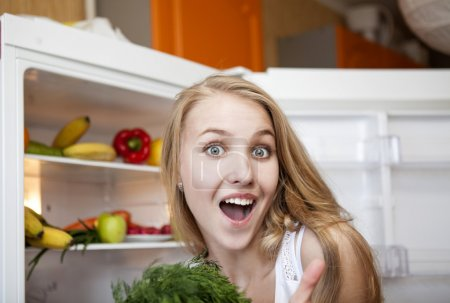Young woman near fridge at home