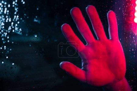 Photo for Dramatic hand in neon lighted window with rain drops. Bright neoned colors. Scary and horror concept. - Royalty Free Image