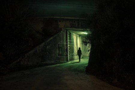 Photo for Lonely woman walking in a dramatic mystic dark alley at night. Danger and scary concept. - Royalty Free Image