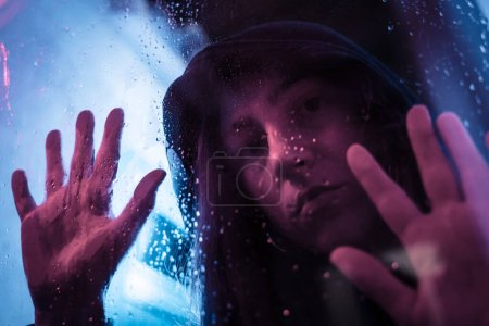 Photo for Beautiful cinematic portrait of stylish young woman in neon lighted window with rain drops. Bright neoned colors. Caucasian model, musician outdoors. Youth culture, scary mist style and music concept. - Royalty Free Image