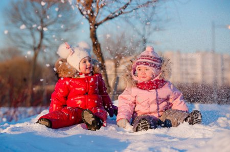 Happy children in winterwear laughing while playing in snowdrift