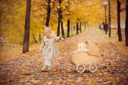 Belle petite fille roule la poussette dans le parc automne