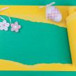 Yellow torn paper with Easter egg and flower on a ...
