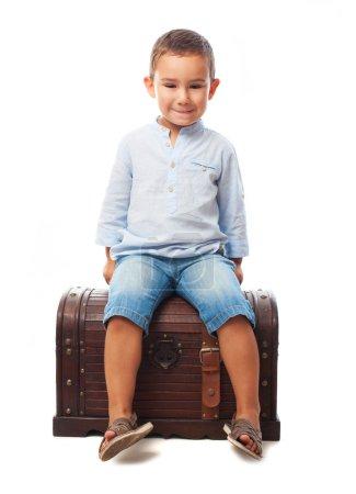 Little boy sitting on wooden trunk
