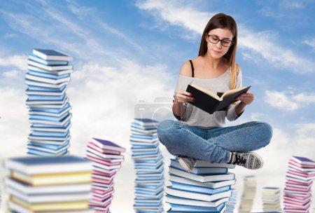 Photo pour Jeune femme lisant un livre assis sur une pile de livres sur le ciel - image libre de droit