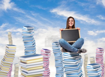 Photo for Young woman holding a blackboard sitting on a books tower - Royalty Free Image