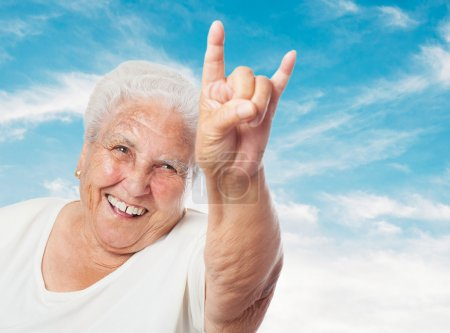 Photo for Portrait of funny old woman doing a rock and roll symbol - Royalty Free Image