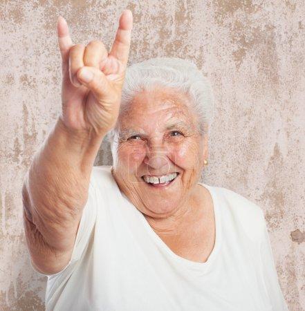 Photo pour Portrait de vieille femme drôle faisant un symbole de rock and roll - image libre de droit