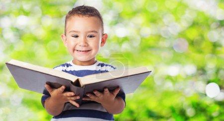 Cute kid holding big book