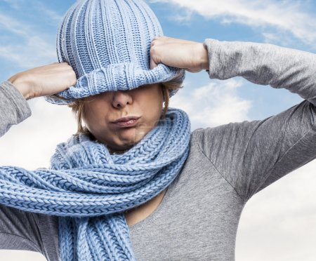 Woman covering head with wool cap