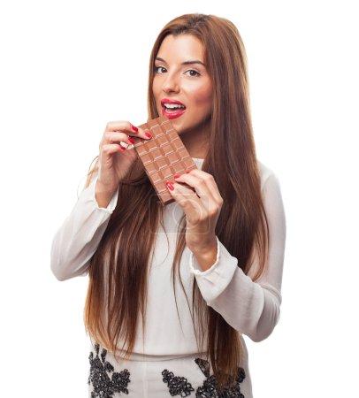 Pretty girl biting a chocolate bar
