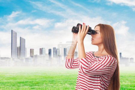 Photo for Portrait of a beautiful young woman looking through the binoculars - Royalty Free Image