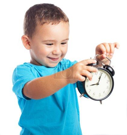 Cheerful child holding  clock