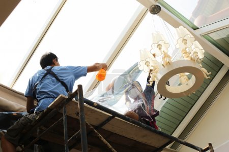 Unidentified  people wrappers tinting a glass house window