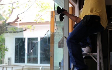 Repair man working on broken glass