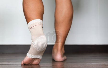 Photo for Man injured ankle and foot wrapped in bandage - Royalty Free Image