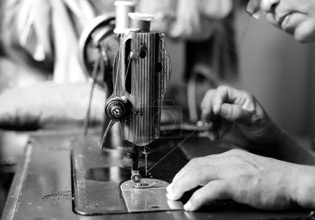 Woman hand threading needle into sewing machine needle